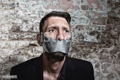 portrait of a midadult man with silver tape over mouth,