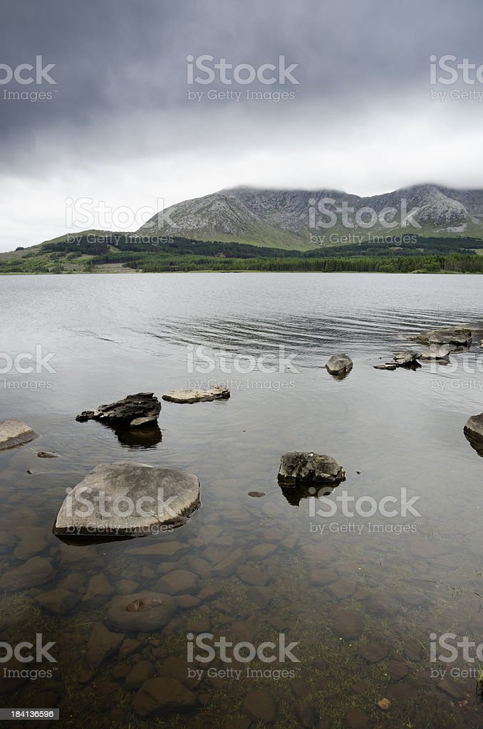 Grey rain clouds over a lake approaching the mountain range in the...