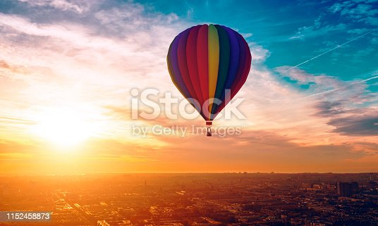 Hot air ballon with different colors travels across the sky. A city is below and rooftops are visible.  Note: The hot air ballon is made in a 3D program. Property release attached.