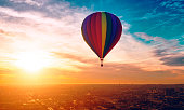 Hot air ballon with different colors travels across the sky. A city is below and rooftops are visible. \nNote: The hot air ballon is made in a 3D program. Property release attached.