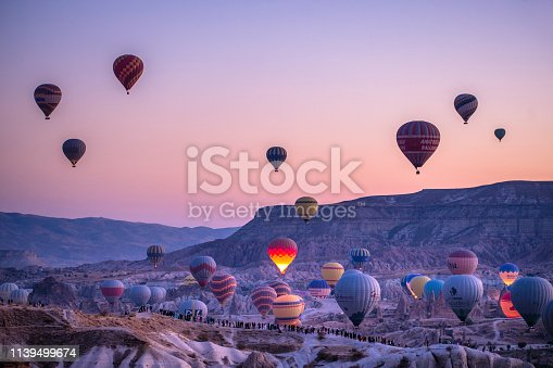 Hot air ballons at Cappadocia, Turkey at sunrise, early in the morning, pink sky, beautiful sunrise. Hot air ballon rising up in the air.