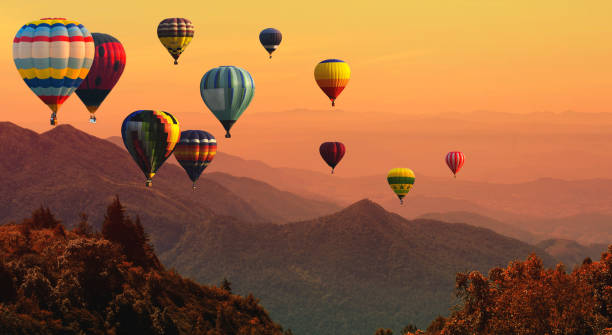 Hot air balloon above high mountain at sunset stock photo