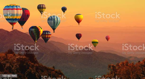 Photo of Hot air balloon above high mountain at sunset