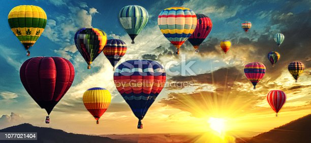 istock Hot air balloon above high mountain at sunset 1077021404