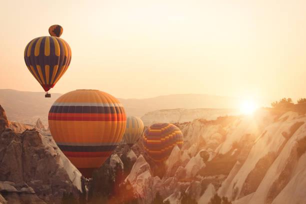 hete luchtballon en fairy schoorstenen in cappadocië - aardpiramide stockfoto's en -beelden