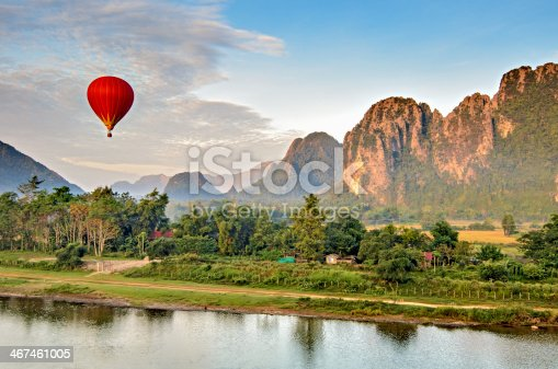 A hot air balloon flying at dawn over the river Nam Song at Vang Vieng, Laos with the scenic backdrop of the karst hill landscape surrounding the town