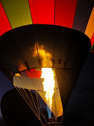 Hot air balloon being inflated by a rush of flames from the gas burner. Colorful balloon being inflated during the Albuquerque Balloon festival.