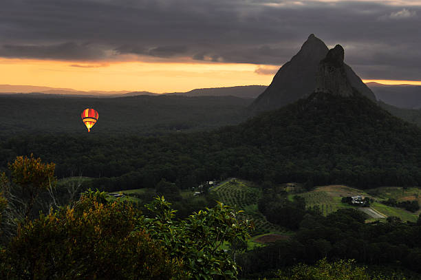 Hot air balloon drifting through the Glasshouse Mountains at dawn stock photo