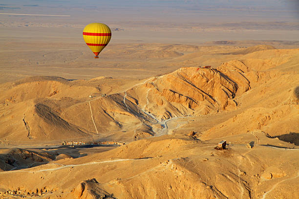Hot Air Balloon Egypt A red and yellow hot air balloon drifts leisurely over the Valley of the Kings in Egypt,.The image is taken from another hot air balloon in the early morning over the Sahara Desert. valley of the kings stock pictures, royalty-free photos & images