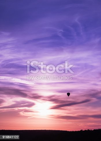 istock Hot air balloon flies in colorful evening sky 916841122