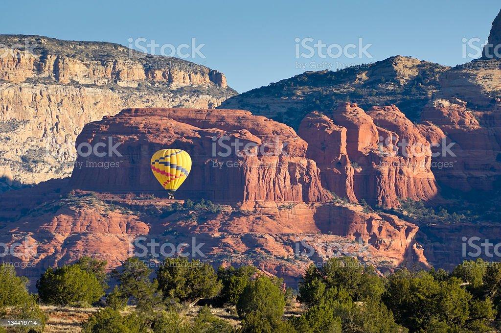 Hot Air Balloon Floating Through Scenic Canyon stock photo