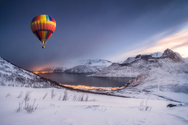 Hot air balloon flying on snow hill with fordgard town in winter stock photo