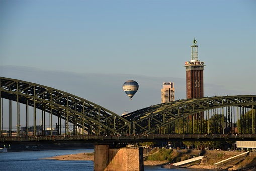 Hot air balloon flying over Hohenzollern Bridge in Cologne