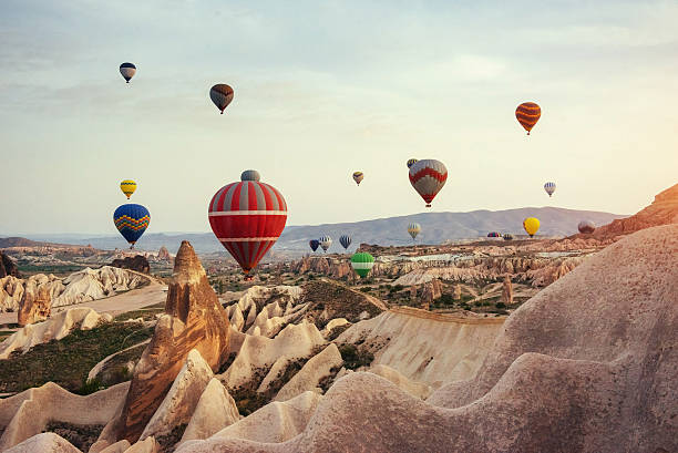 Hot air balloon flying over rock landscape at Cappadocia Turkey. Hot air balloon flying over rock landscape at Cappadocia Turkey. Cappadocia with its valley, ravine, hills, located between the volcanic mountains in Goreme National Park. anatolia stock pictures, royalty-free photos & images