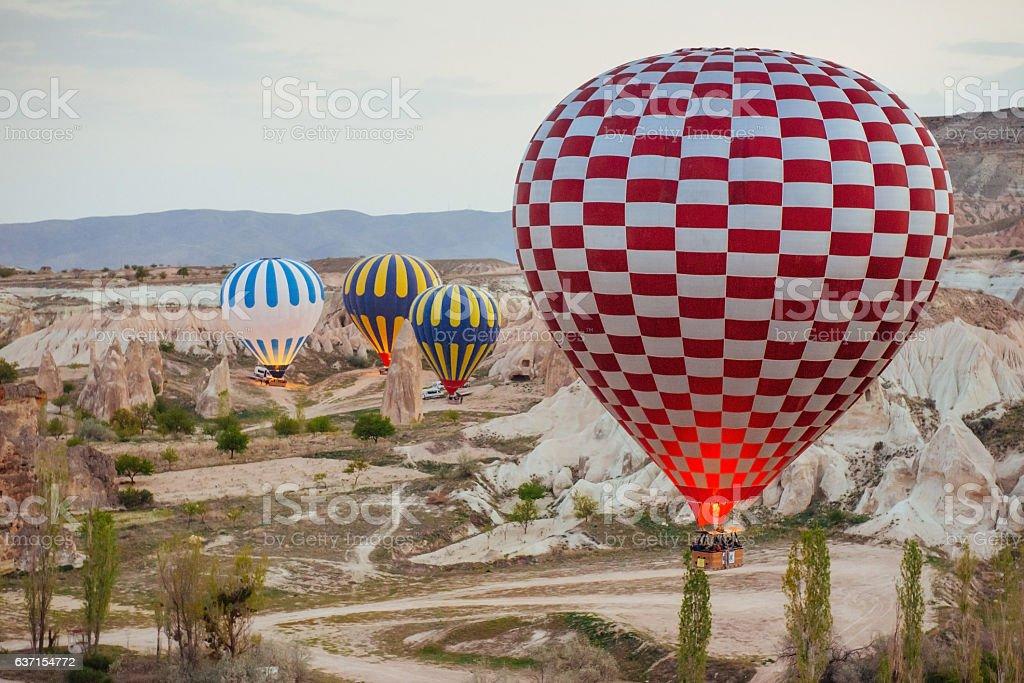 Hot air balloon flying over rock landscape at Turkey. Cappadocia stock photo