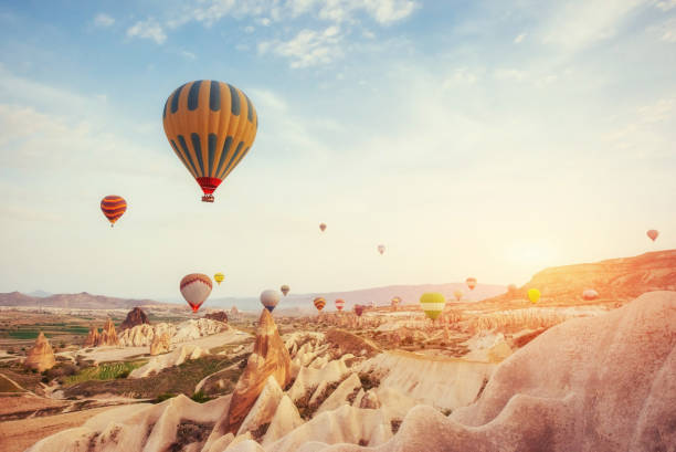 hot air balloon flying over rock landscape at turkey. cappadocia - hot air balloon стоковые фото и изображения