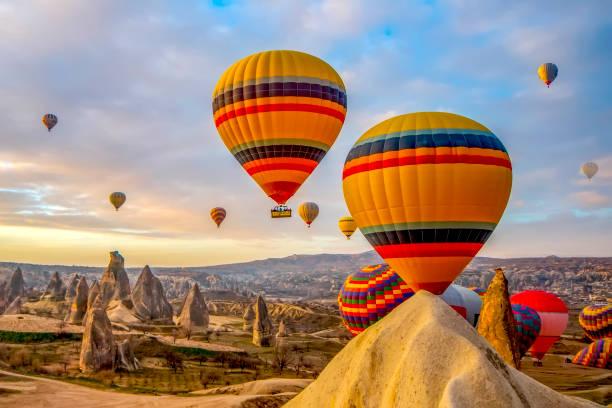 hete luchtballon vliegen over spectaculaire cappadocië - aardpiramide stockfoto's en -beelden