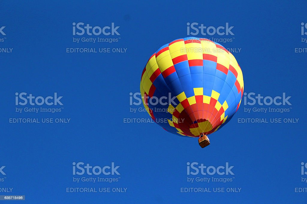 Hot air balloon from below against solid blue sky, royalty-free stock photo