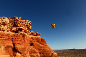 a hot air balloon floats over Arches National Park near Moab Utah.