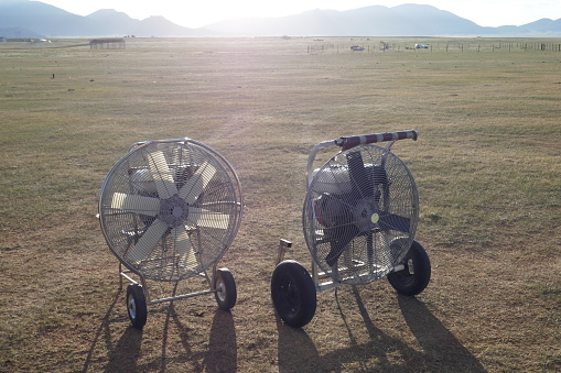 Hot air balloon inflation fans in sunny outdoor field
