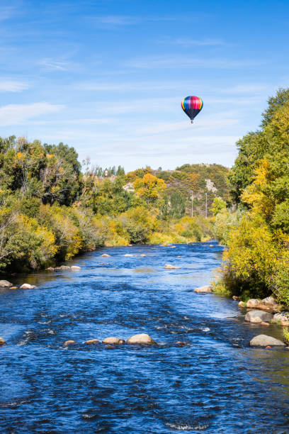 Hot air balloon over blue river and trees changing color on still Autumn morning Trees are starting to turn yellow in autumn as a hot air balloon floats above a calm blue river near Steamboat Springs, Colorado. steamboat springs stock pictures, royalty-free photos & images