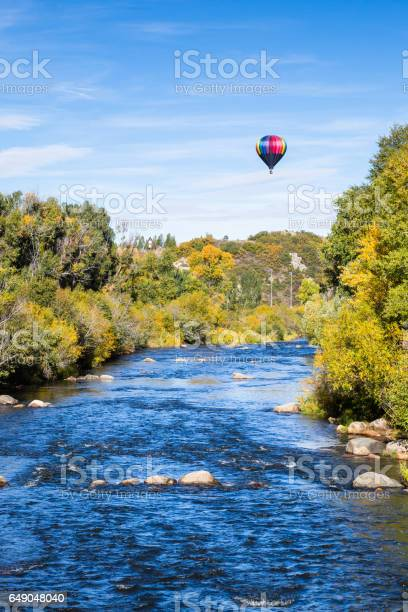 Photo of Hot air balloon over blue river and trees changing color on still Autumn morning