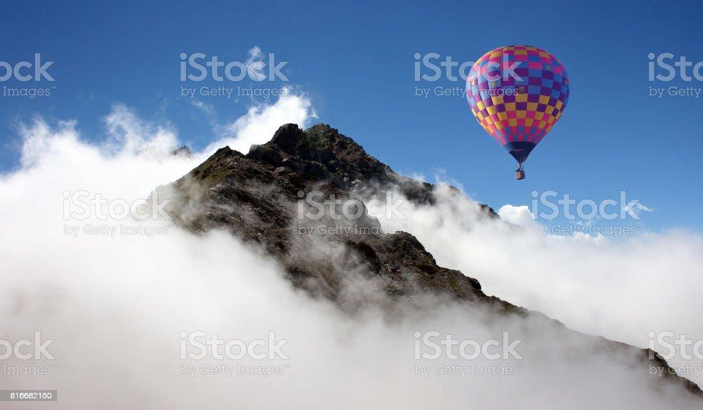 Hot air balloon over mountains stock photo
