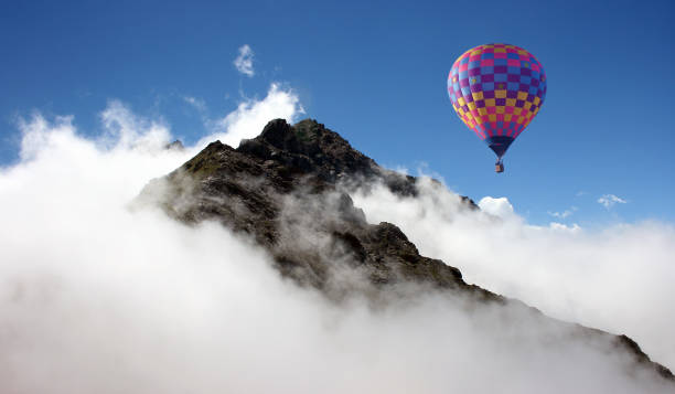 Hot air balloon over mountains stock photo