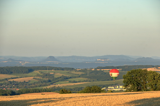 Saxony, Germany, Juli 24 2019: Hot air balloon over the field with blue sky in front of saxony switzerland