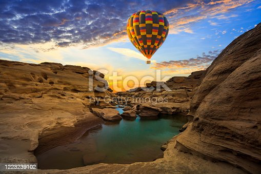 Hot air balloon over the sea at amazing sunset - Long exposure image of Dramatic sky and seascape with rock