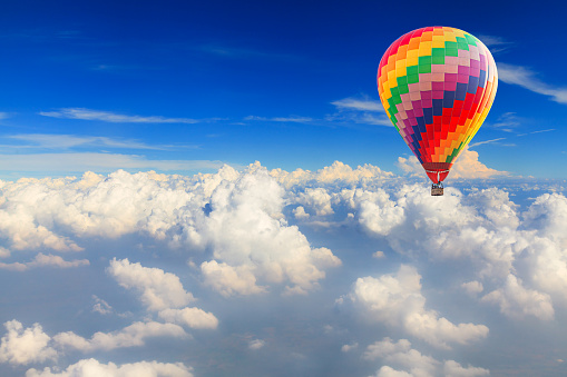 Hot air balloon over the white cloud on blue sky