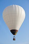 White hot air balloon on the blue sky.