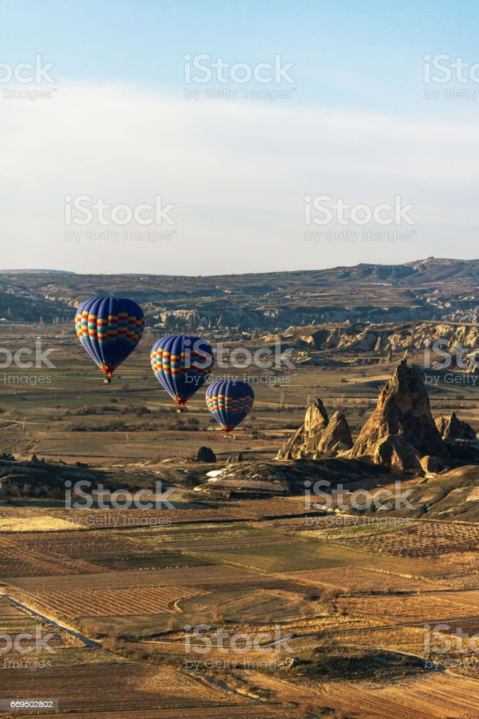 hot air balloon rises very high in blue sky above white clouds, bright sun shines stock photo