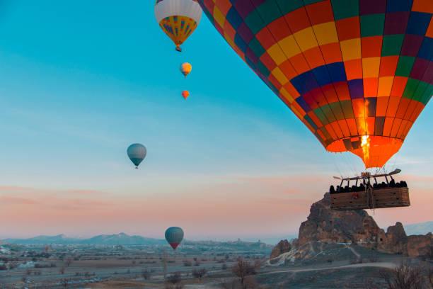 Heißluftballon erhebt sich sehr hoch im blauen Himmel über weißen Wolken, helle Sonne scheint – Foto