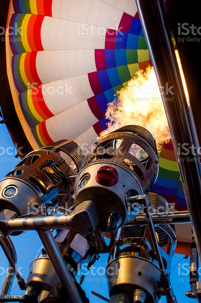 Hot air balloon with huge flame in foreground stock photo