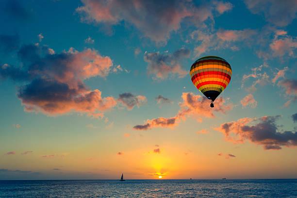 воздушный шар на закате на фоне моря - hot air balloon стоковые фото и изображения