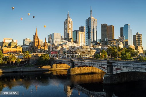 Hot air balloons floating above the Melbourne skyline at dawn.