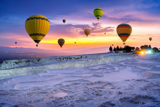 Hot air balloons and Natural travertine pools at sunset in Pamukkale, Turkey. stock photo