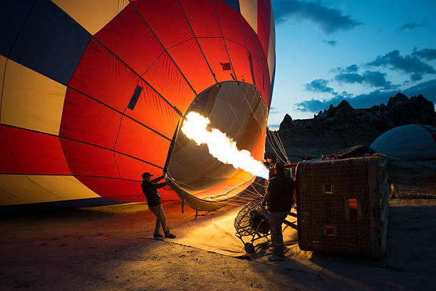 Hot air balloons and workers Cappadocia, Turkey - July 21, 2016: Hot air balloons in Cappadocia. Hot air balloons carrying tourists rise over the rugged landscape of Cappadocia / Turkey in the early morning. tuff stock pictures, royalty-free photos & images