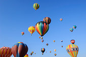 Isolated image of hot air balloons flying in the air with clouds in the background.\n\nTaken in Reno, Nevada, USA.