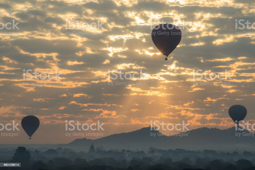 Hot air balloons fly over the Bagan plains during the sunrise in Bagan archaeology zone, Mandalay region of Myanmar. royalty-free stock photo