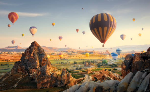 Hot Air Balloons Flying at Sunset, Cappadocia, Turkey. Beautiful morning scenic with a balloon flight over the spectacular Cappadocia, Turkey. turkish stock pictures, royalty-free photos & images