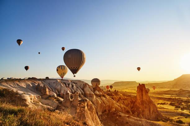 l'air chaud des ballons voler au coucher du soleil, cappadoce, turquie - montgolfière photos et images de collection