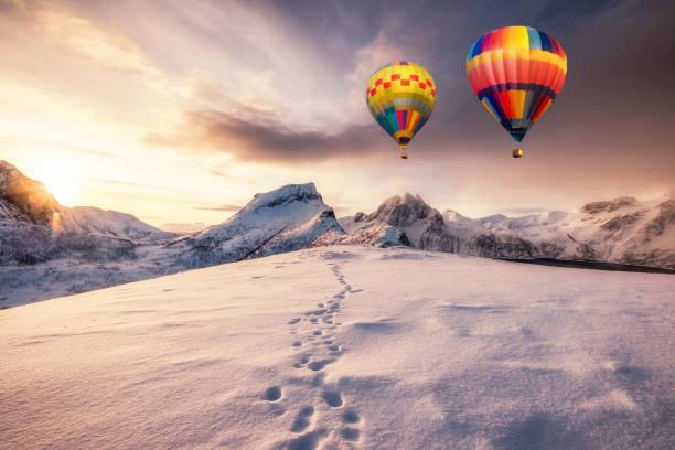 Hot air balloons flying on snowy mountain with footprint on peak stock photo