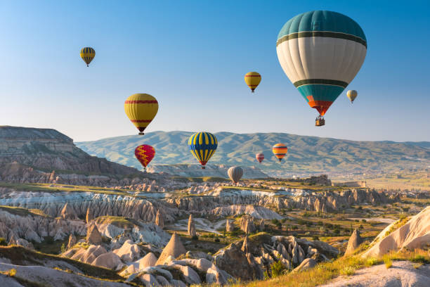 Hot air balloons flying over Cappadocia, Turkey Hot air balloons flying in sunset sky Cappadocia, Turkey turkish stock pictures, royalty-free photos & images