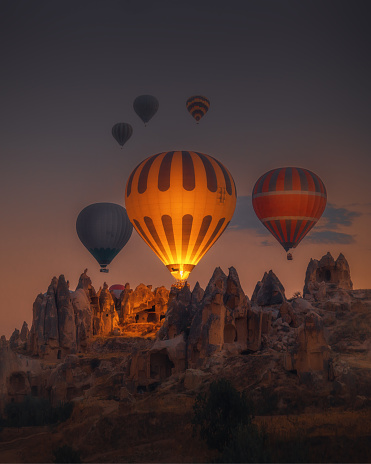 Spectacular sunset landscape view of hot air balloon illuminated with fire in sky tour over amazing fairy chimneys rock forms on valleys and fields in early morning in Kapadokya, Göreme National Park, Turkiye. Dreamy nature background.