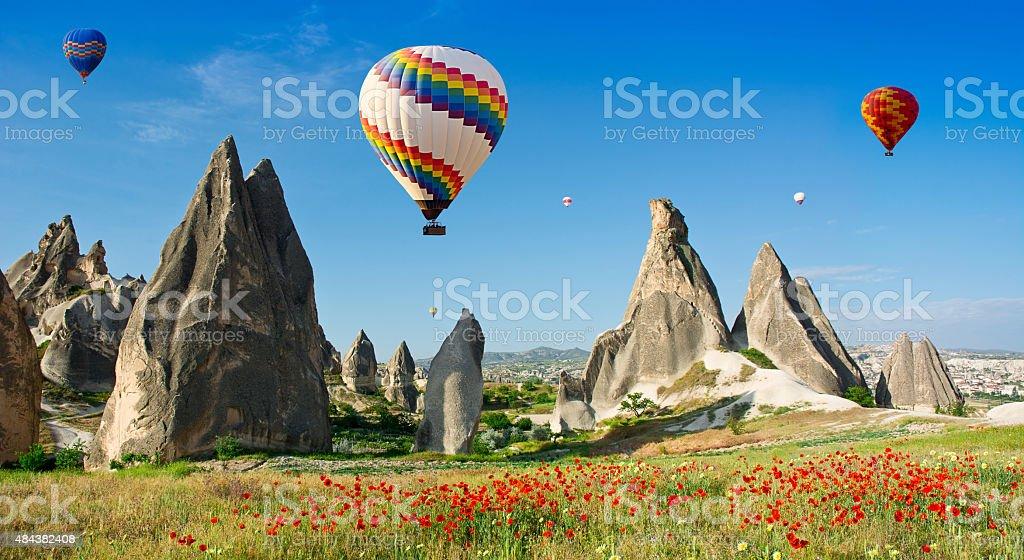 Hot air balloons flying over rock landscape at Cappadocia stock photo
