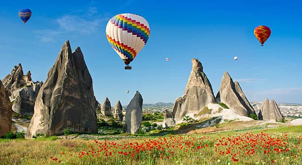 hot air balloons flying over rock landscape at cappadocia - aardpiramide stockfoto's en -beelden
