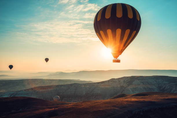 hot air balloons flying over the valley at cappadocia, turkey - blowing stock photos and pictures