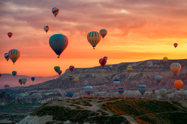 Hot Air balloons flying tour over Mountains landscape spring sunrice Cappadocia, Goreme Open Air Museum National Park, Turkey nature background. stock photo